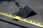 Computer Crime Scene. A laptop computer that was on fire on a road behind CRIME SCENE DO NOT CROSS P poster