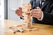 Alternative Risk Concept, Plan And Strategy In Business Protect With Balance Wooden Stack With Hand poster