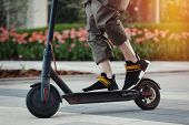 Close Up Of Man Riding Black Electric Kick Scooter At Beautiful Park Landscape poster