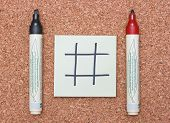 Blank Tic Tac Toe Game On Sticky Note With Red And Black Markers On Cork