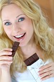 foto of stressless  - Blond woman eating chocolate bar - JPG