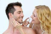 Mulher aplicar protetor solar no rosto do namorado