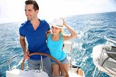 pic of ship steering wheel  - Young couple navigating on a yacht in caribbean sea - JPG