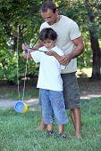 Постер, плакат: Отец играя с сыном с Диаболо
