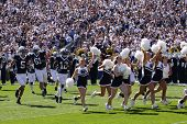 Penn State players and cheerleaders run onto the field against Illinois