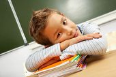 Portrait of cute lad keeping his head on stack of copybooks in classroom