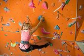 The girl is engaged in rock climbing on the climbing gym