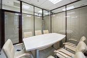 Light office blinds closed with a table and leather chairs