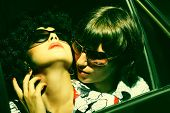Loving couple embraces in the car. Fashionable young couple wearing sunglasses.  Art photo