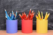 Closeup of colored pencils in matching pencil cups in front of a school room chalkboard. The cups are covered in red, blue and yellow construction paper and filled with the same color pencil.