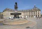 BORDEAUX, FRANCE - JUNE 27: People walks on the Place de la Bourse in Bordeaux, France on June 27, 2013. The fountain of Three Graces in the center of square was erected in 1869