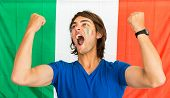 picture of clenched fist  - Young Fan of the Italian team standing in front of an Italian Flag - JPG
