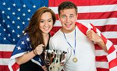 Two Americans posing as athletes, being supporters of their national team, holding an American Flag