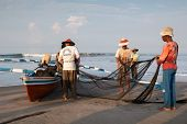 PADANG - AUGUST 25: Fishermen work as a team harvest the fish caught in the fishing nets in Padang,