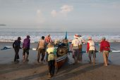 PADANG - AUGUST 25: Fishermen work as a team launch the boat to sea in Padang, West Sumatera, Indone