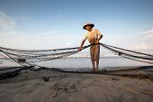 PADANG - AUGUST 25: A fisherman folds up the fishing nets in preparation for the next cast in Padang