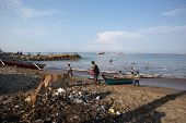 PADANG - AUGUST 25: A fisherman takes his boat to shore in a busy fishing village in Padang, West Su