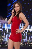 Young Woman In A Red Dress Talks On The Phone While Out In The City At Night.