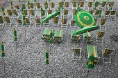 Green And Yellow Beach Umbrellas And Deckchairs On Stony Beach in Camogli