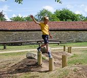 stock photo of chute  - Young boy balancing on obsticle course  in playground - JPG