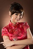 Attractive Chinese woman dress traditional cheongsam at New Year, closeup studio shot.