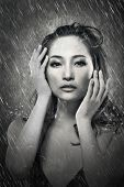 Attractive sexy asian lady in the rain, in bikini. Black and white portrait.