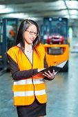 Logistics - female worker or supervisor using tablet computer at warehouse of freight forwarding company