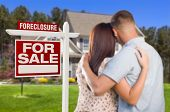 Military Couple in Front of House and Foreclosure For Sale Real Estate Sign.