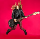 Blond Rock and roll girl jumping playing bass guitar on red background
