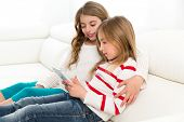 Children sister friends kid girls playing together with tablet pc on white sofa