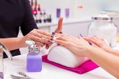 stock photo of fingernail  - Nails saloon woman nail polish remove with tissue for new manicure - JPG