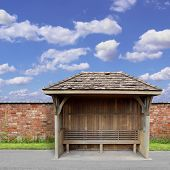 An Old Wooden Bus Shelter with Red Brick Wall and Blue Sky