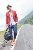 beautiful young fashion man posing outdoor on the side of the road, with a bag in his hand while holding a hand in his pocket and looking into the camera