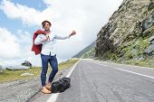 portrait of a young fashion man hitchhiking in the mountains with a smile on his face