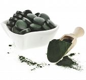 Spirulina algae  powder and tablets in spoon , isolated on white background