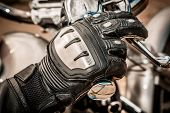 Human hand in a Motorcycle Racing Gloves holds a motorcycle throttle control. Hand protection from f