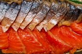 Smoked mackerel and trout cut on a platter closeup