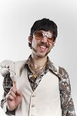 pic of cheeky  - Portrait of a retro man in a 1970s leisure suit and sunglasses smiling to the camera - JPG
