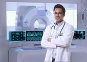 Portrait of asian doctor in MRI room at hospital, looking at camera, smiling.