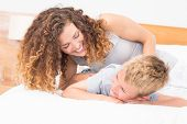 Happy mother tickling her son on bed at home in bedroom