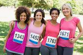Portrait of happy female participants of breast cancer marathon in park