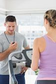 Woman exercising on treadmill and being timed by a personal trainer at gym