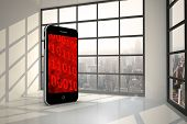 Binary code on smartphone screen against room with large window showing city
