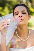 Close-up of a young beautiful bride blowing soap bubbles in the park