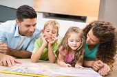 stock photo of storybook  - Cute siblings lying on the rug reading storybook with their parents at home in living room - JPG