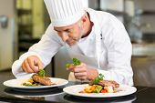 stock photo of concentration man  - Closeup of a concentrated male chef garnishing food in the kitchen - JPG