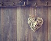 Rustic heart decoration hanging from hook on wood panel wall - vintage tone effect added