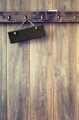 Blank slate sign hanging on rustic wooden wall - vintage tone effect added to wood