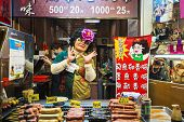 JIUFEN, TAIWAN - JANUARY 17, 2013: A food vendor poses with her goods. The town is a renowned touris