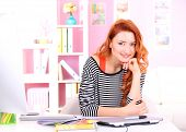 Young woman graphic designer working using pen tablet in workplace